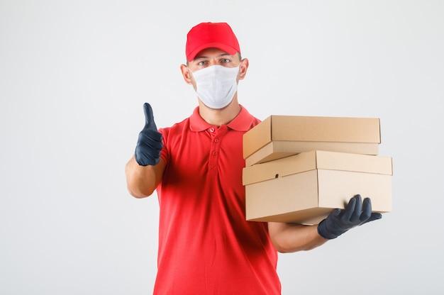 Entregador de uniforme vermelho, máscara médica, luvas segurando caixas de papelão e mostrando o polegar Foto gratuita