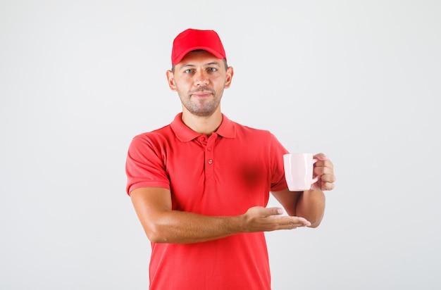 Entregador de uniforme vermelho segurando um copo de bebida e sorrindo Foto gratuita