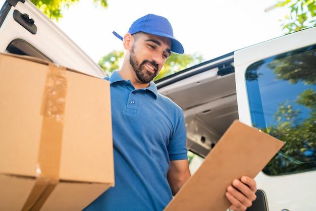 Entregador, descarregando caixas de papelão da van. Foto Premium