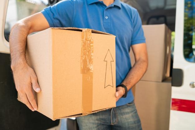 Entregador, descarregando caixas de papelão da van Foto Premium