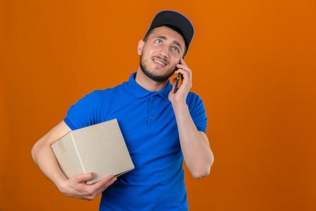 Entregador descontente de jovem vestindo camisa pólo azul e boné em pé com uma caixa de papelão falando no celular com o rosto infeliz mostrando antipatia sobre um fundo laranja Foto gratuita