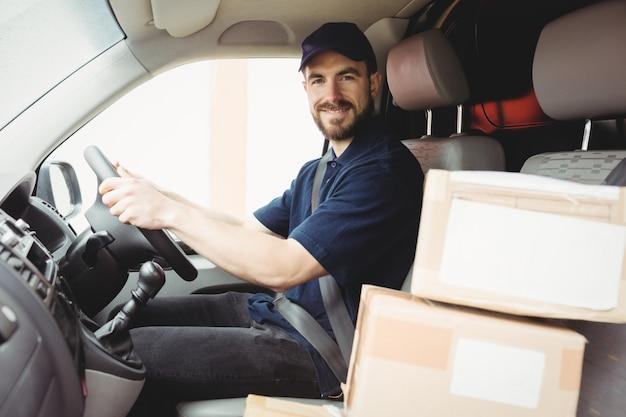 Entregador dirigindo sua van com pacotes no banco da frente Foto Premium
