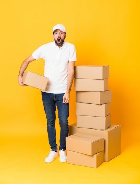 Entregador entre caixas com expressão facial de surpresa Foto Premium