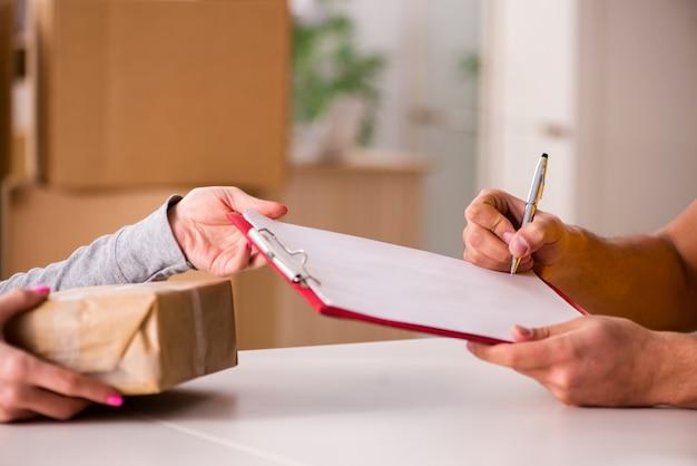 Entregador entregando caixa de encomendas Foto Premium