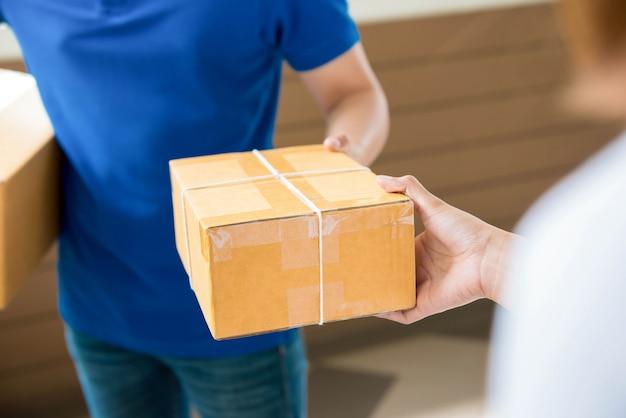 Entregador entregando uma encomenda para uma mulher Foto Premium