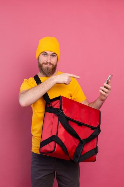 Entregador europeu alegre com bolsa casual segurando telefone apontando dedo na tela rosa Foto gratuita