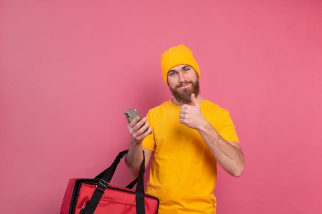 Entregador europeu alegre com bolsa casual segurar telefone rosa Foto gratuita