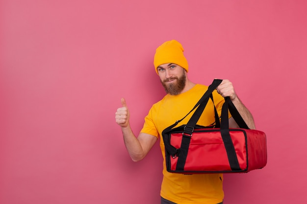 Entregador europeu barbudo com caixa com comida sorrindo e mostrando o polegar rosa Foto gratuita