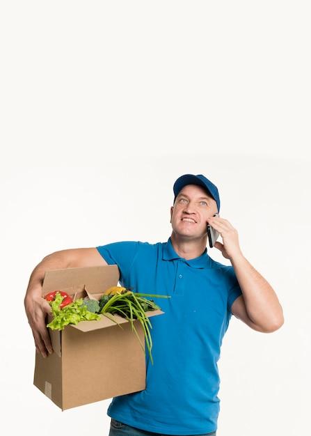 Entregador, falando no telefone e segurando a caixa de supermercado Foto gratuita
