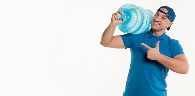 Entregador feliz apontando para garrafa de água e sorrindo Foto gratuita