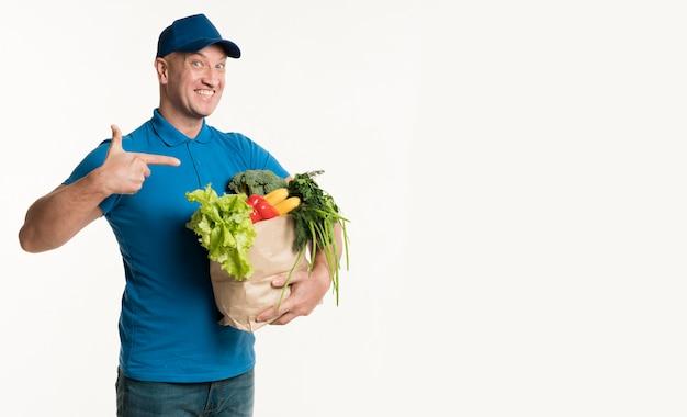 Entregador feliz apontando para sacola de compras na mão Foto gratuita