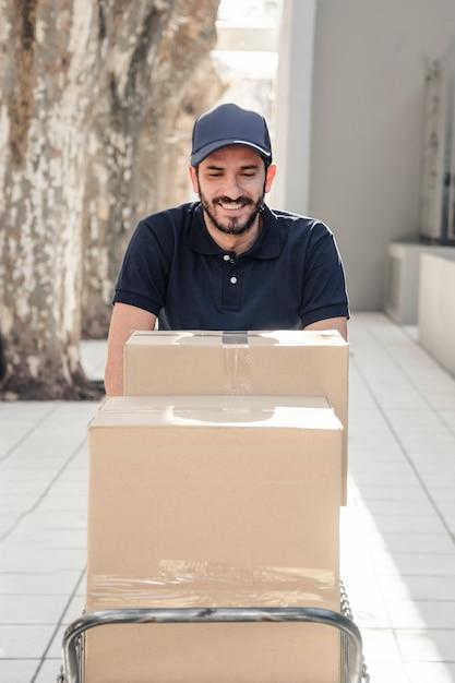 Entregador feliz com caixas de papelão Foto gratuita