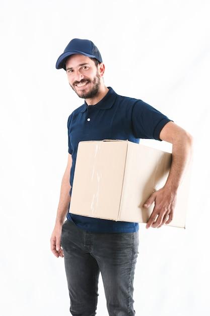 Entregador feliz com parcela no fundo branco Foto gratuita