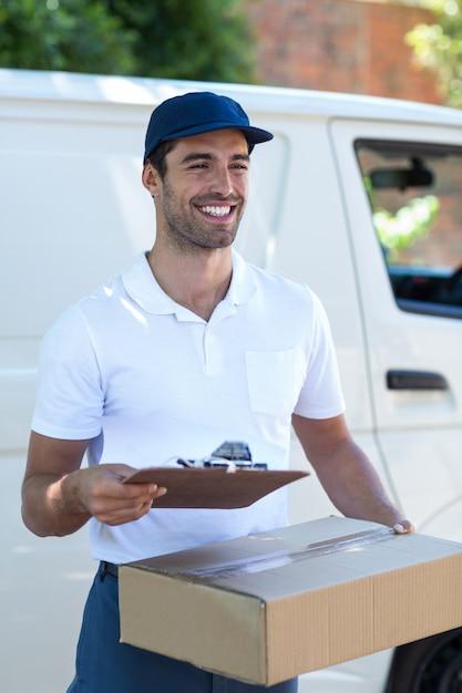 Entregador feliz com prancheta e caixa de papelão Foto Premium