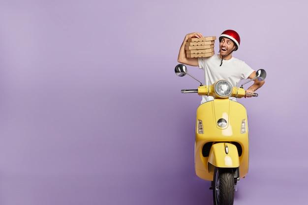 Entregador feliz dirigindo scooter segurando caixas de pizza Foto gratuita