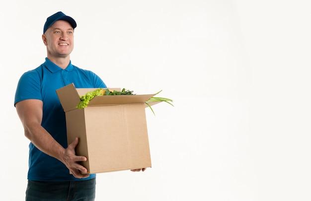 Entregador feliz segurando caixa de supermercado Foto gratuita