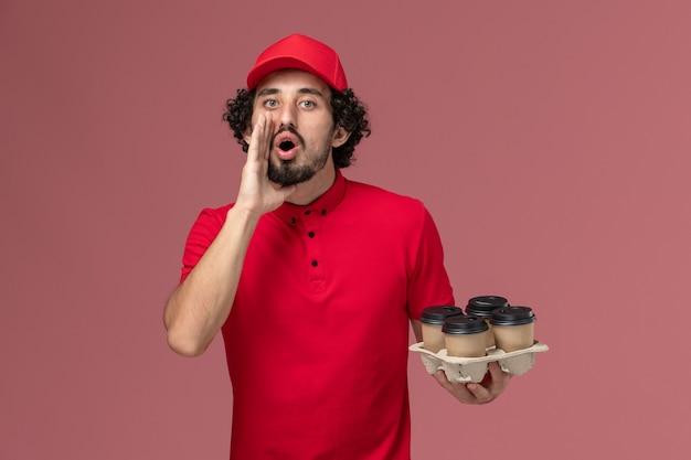 Entregador masculino de camisa vermelha e capa, vista frontal, segurando xícaras de café marrons e chamando funcionário de entrega de serviço de parede rosa claro Foto gratuita