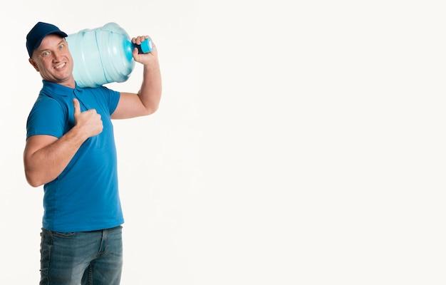Entregador, mostrando os polegares e carregando a garrafa de água Foto gratuita