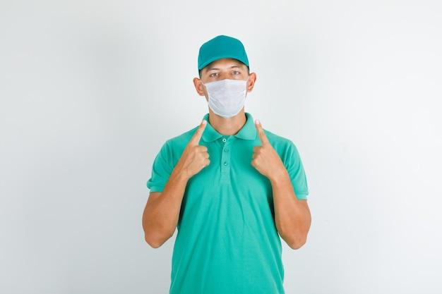 Entregador mostrando sua máscara médica em camiseta verde com tampa Foto gratuita