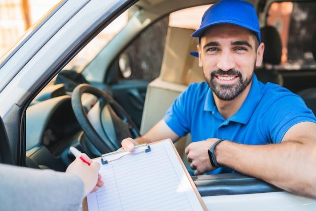 Entregador na van enquanto cliente assinar na área de transferência Foto Premium