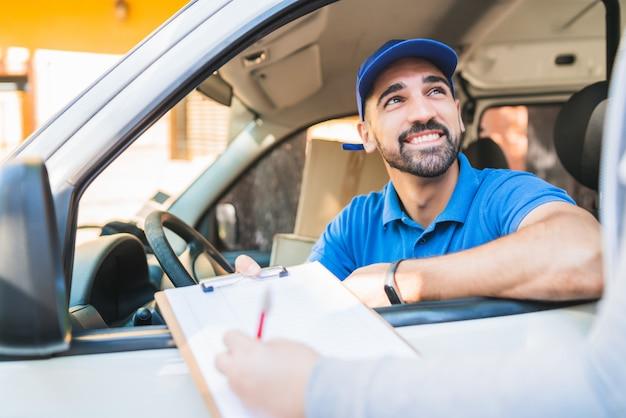 Entregador na van, enquanto o cliente assina a área de transferência. Foto Premium