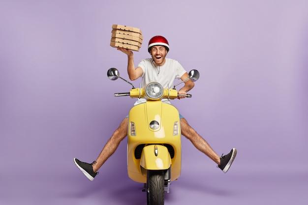 Entregador ocupado dirigindo scooter segurando caixas de pizza Foto gratuita