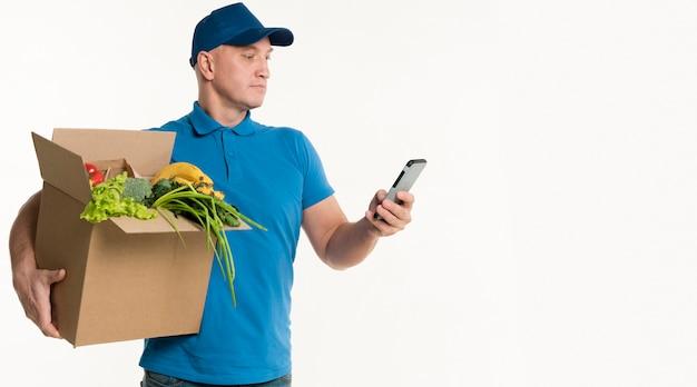 Entregador, olhando para o smartphone enquanto carregava caixa de supermercado Foto gratuita