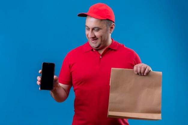 Entregador satisfeito vestindo uniforme vermelho e boné segurando um pacote de papel mostrando um celular sorrindo com uma cara feliz em pé sobre um fundo azul Foto gratuita