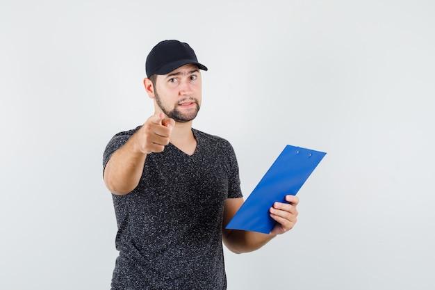 Entregador segurando a prancheta enquanto aponta para a câmera em vista frontal de t-shirt e boné. Foto gratuita
