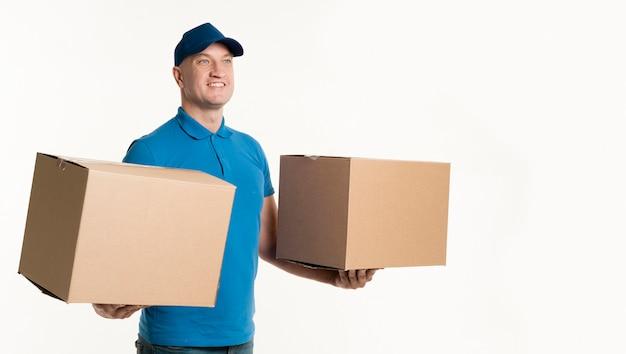 Entregador, segurando caixas de papelão em cada mão Foto gratuita