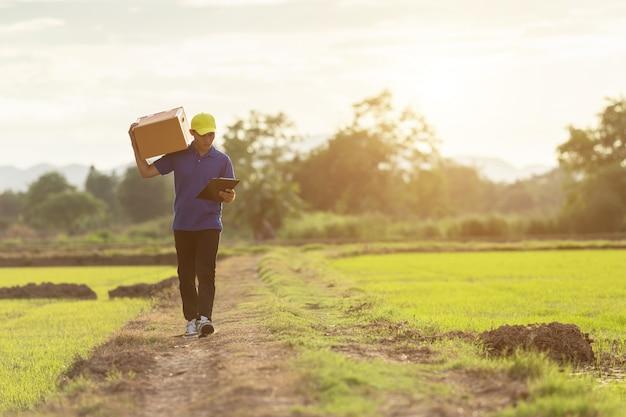 Entregador segurando marrom parcela ou entrega de caixas de papelão ao cliente no campo Foto Premium