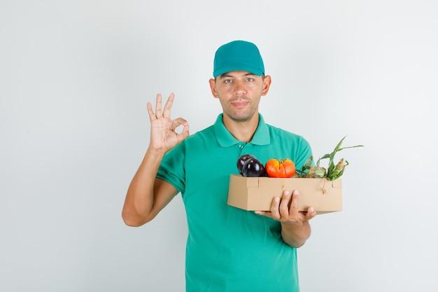 Entregador segurando uma caixa de vegetais com sinal de ok, camiseta verde e boné Foto gratuita