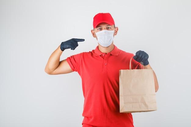 Entregador segurando uma sacola de papel e apontando para si mesmo em uniforme vermelho, máscara médica e luvas Foto gratuita