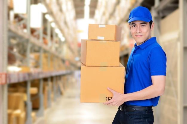 Entregador sorridente que transporta caixas no fundo do armazém em borrão Foto Premium