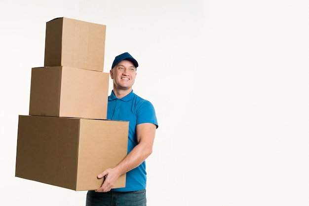 Entregador sorridente segurando caixas de papelão com espaço de cópia Foto gratuita