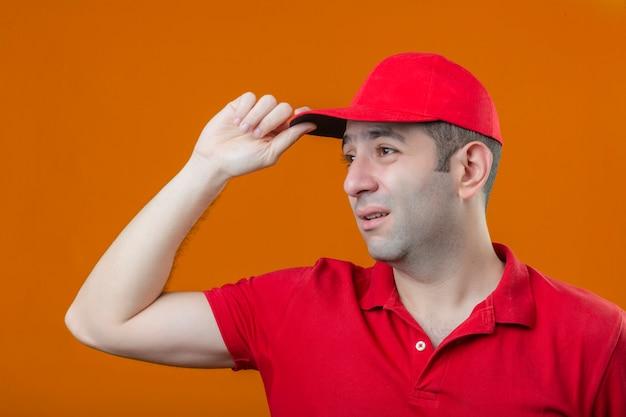 Entregador triste e triste, com uma camisa pólo vermelha e boné olhando de lado sobre um fundo laranja isolado Foto gratuita