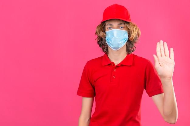 Entregador vestindo camisa pólo vermelha e boné com máscara médica, em pé com a mão aberta, fazendo sinal de pare com gesto de defesa de expressão sério e confiante sobre fundo rosa isolado Foto gratuita