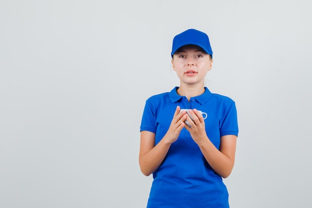 Entregadora de camiseta azul e boné segurando um copo de bebida Foto gratuita