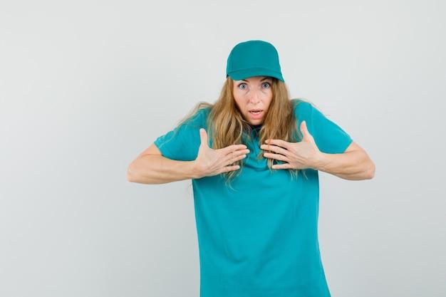 Entregadora de camiseta, boné apontando para si mesma ao me perguntar e parecendo agitada Foto gratuita