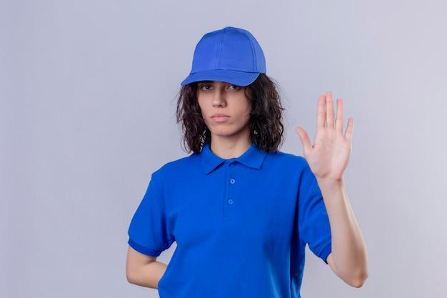 Entregadora de uniforme azul e boné em pé com a mão aberta fazendo sinal de pare com gesto de defesa de expressão sério e confiante Foto gratuita