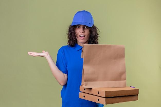 Entregadora de uniforme azul segurando caixas de pizza e um pacote de papel parecendo incerta e confusa, sem resposta, espalhando as palmas das mãos em pé sobre o espaço verde oliva Foto gratuita