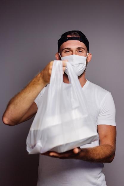 Entregar um homem segurando um saco plástico com comida na porta Foto gratuita