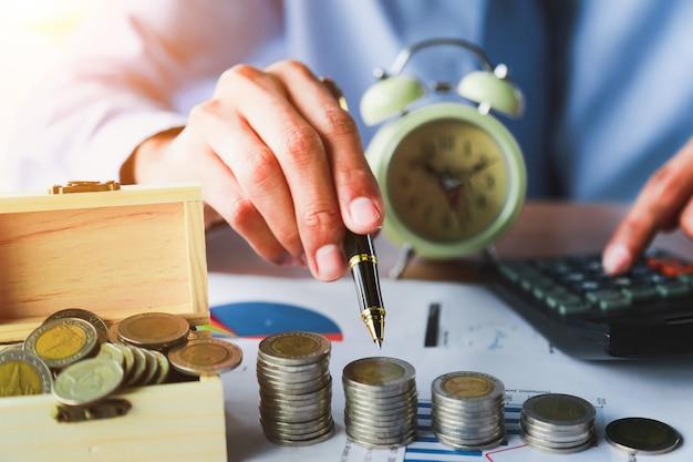 Entregue a colocação de moedas do dinheiro empilhe no dinheiro da economia e no conceito crescente do negócio. Foto Premium