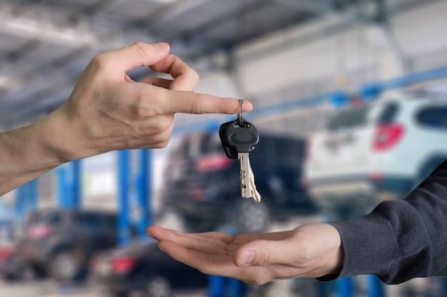 Entregue a entrega de chaves do carro com o dedo e a mão que recebe no centro de serviço da garagem Foto Premium