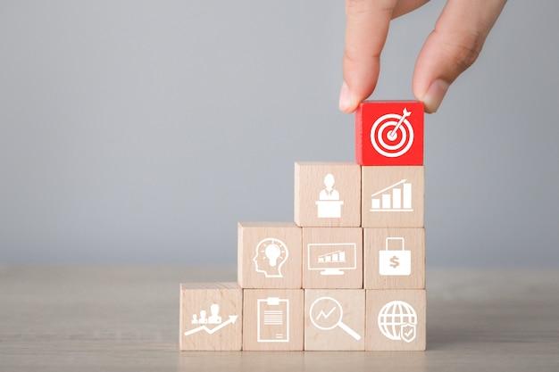 Entregue a organização do bloco de madeira que empilha com seta e negócio do ícone, alvejando o conceito do negócio. Foto Premium