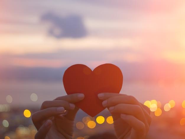 Entregue guardar o coração bonito durante o fundo do por do sol. Foto Premium