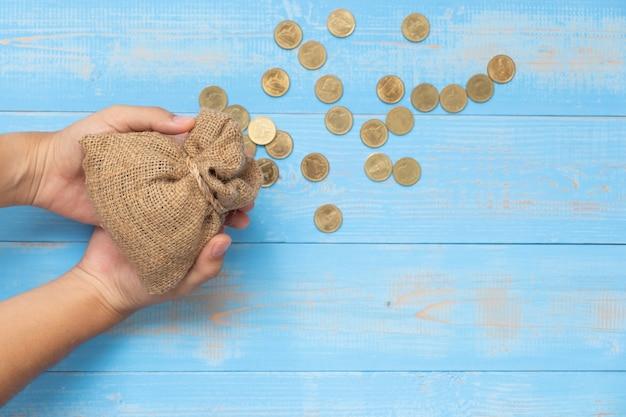 Entregue guardar o saco ou o saco do dinheiro com as moedas no fundo de madeira azul. Foto Premium