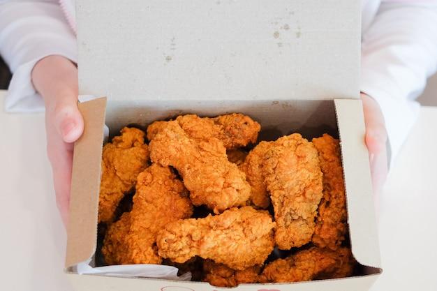 Entregue guardar pilões & asas friáveis deliciosos de frango frito para o petisco. Foto Premium