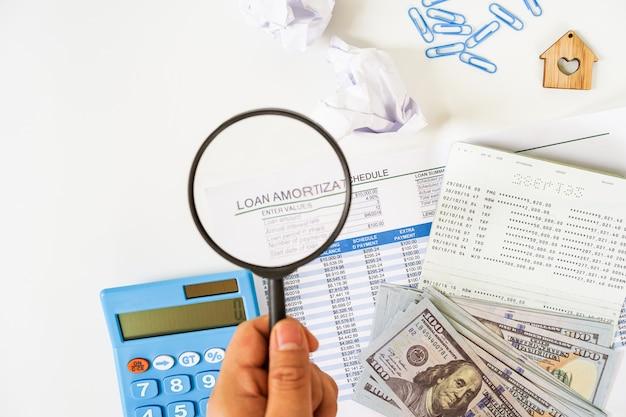 Entregue guardar uma lupa sobre a folha da programação de empréstimo, nós cédula, calculadora, configuração lisa da caderneta bancária no fundo branco. Foto Premium