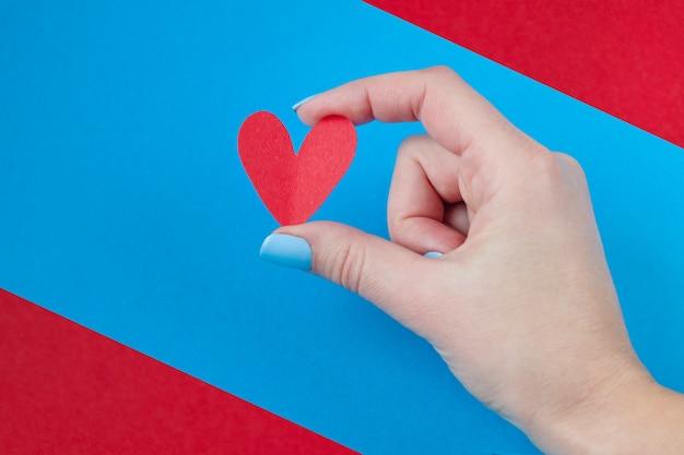 Entregue guardarar um coração vermelho em um fundo vermelho e azul. plano de fundo para o dia dos namorados Foto Premium